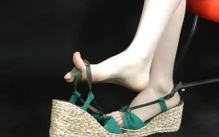 Asian feet showing in wedge espadrille style sandals. Zoom.
